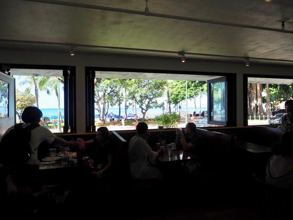 窓際のテーブルはカラカウア通りに面している